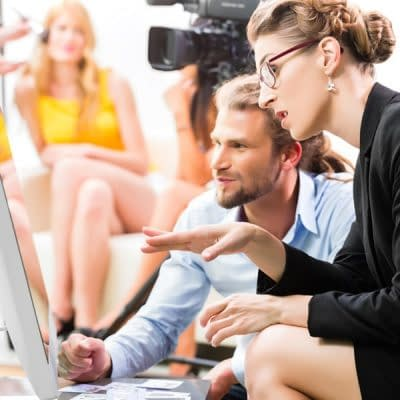 image of a businessman and woman at a computer while people are filming in the background